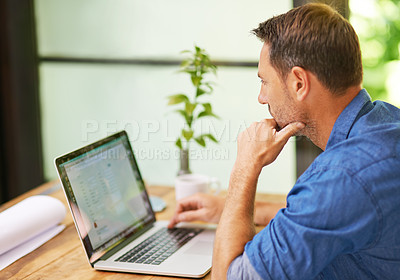 Buy stock photo Shot of a man working on his laptop at home