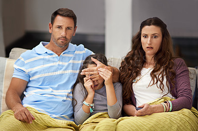 Buy stock photo Shot of a father covering his daughter's eyes while watching a movie at home