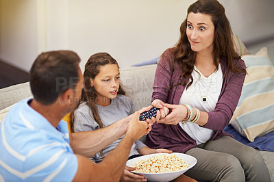 Buy stock photo Cropped shot of a young family watching a movie from the sofa