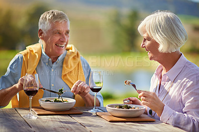 Buy stock photo Cropped shot of a senior couple drinking wine while enjoying a meal outdoors