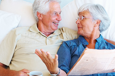 Buy stock photo Senior couple reading newspaper and happy with the news
