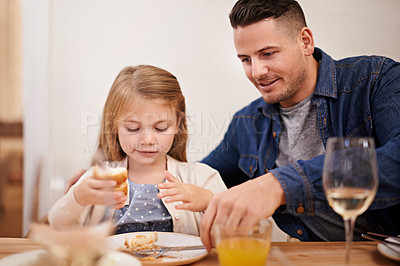 Buy stock photo Cropped shot of a young father and his daughter sitting down to family dinner