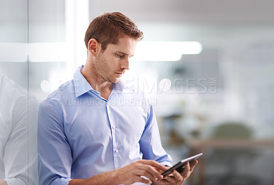 Buy stock photo Shot of a young businessman standing in an office using a digital tablet
