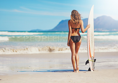 Buy stock photo Rearview shot of a young surfer standing on the beach