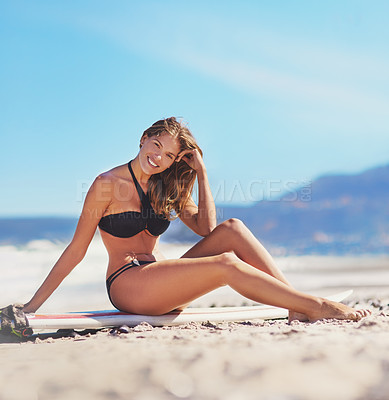 Buy stock photo Shot of a sexy young woman sitting on her surfboard at the beach