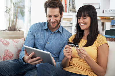 Buy stock photo Cropped shot of a couple using a digital tablet at home