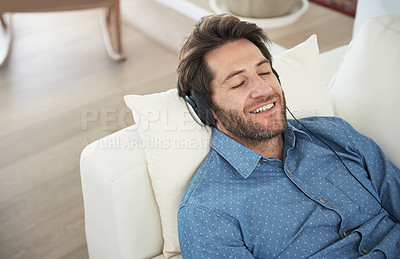 Buy stock photo Cropped shot of a man listening to music while relaxing on the sofa at home