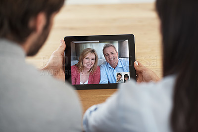 Buy stock photo Cropped shot of a couple chatting to their senior parents online