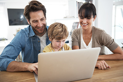 Buy stock photo Cropped shot of a young family using a laptop together at home