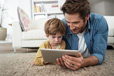 Buy stock photo Shot of a young father and son using a tablet together at home