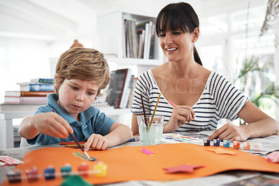 Buy stock photo Shot of a mother watching her little boy painting at home