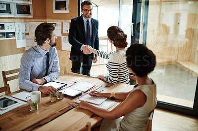 Buy stock photo Shot of two businesspeople shaking hands in an office while colleagues look on