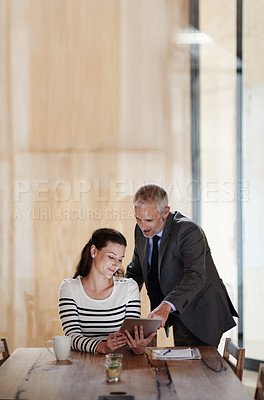Buy stock photo Shot of colleagues using a digital tablet together in an office