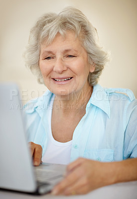 Buy stock photo A senior woman working on her laptop and smiling