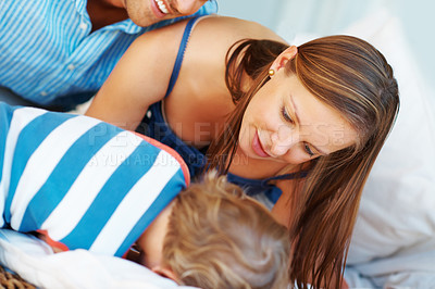 Buy stock photo Little boy lying on sofa with mother and father looking at him