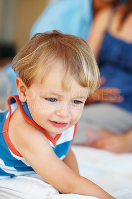 Buy stock photo Closeup portrait of young boy sitting on a sofa with parents in background