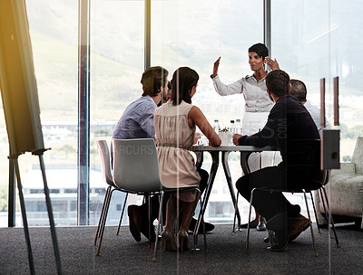 Buy stock photo Shot of a businesswoman giving a presentation to a group of colleagues in a boardroom