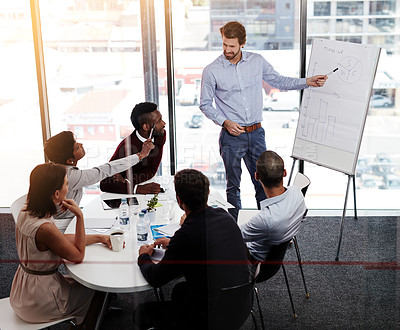 Buy stock photo Shot of a businessman giving a whiteboard presentation to a group of colleagues in a boardroom