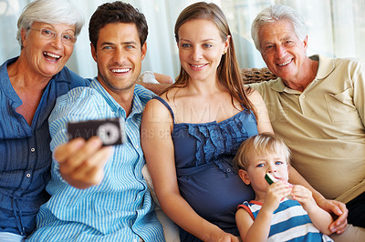 Buy stock photo Portrait of man holding cellphone and showing images to his family