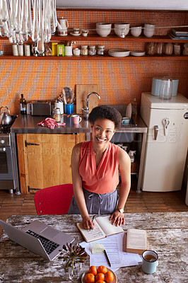Buy stock photo Portrait of a young woman writing in a diary while working in her kitchen