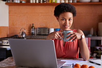 Buy stock photo Portrait of a young woman drinking a coffee while working on a laptop in her kitchen