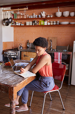 Buy stock photo Shot of a young woman working on a laptop and writing in a diary in her kitchen
