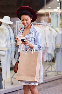 Buy stock photo Cropped shot of a young woman sending a text while shopping