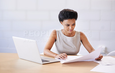 Buy stock photo Shot of a female architect sitting at her desk with a blueprint and her laptop