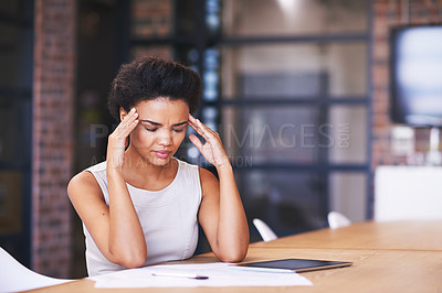 Buy stock photo Shot of a businesswoman looking stressed while working at her desk
