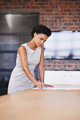 Buy stock photo Shot of a female architect studying a blueprint