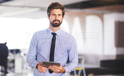 Buy stock photo Shot of a young executive using a digital tablet while standing in his office