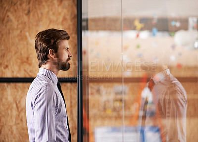 Buy stock photo Shot of a young executive looking through a glass wall while standing in the office