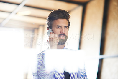 Buy stock photo Shot of a young executive talking on his cellphone while standing in the office