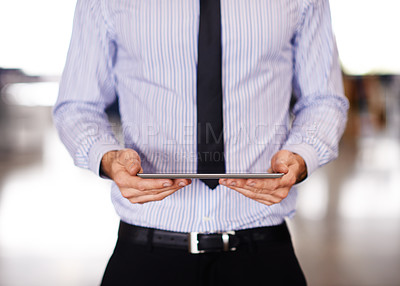 Buy stock photo Shot of a businessman using a digital tablet while standing in his office