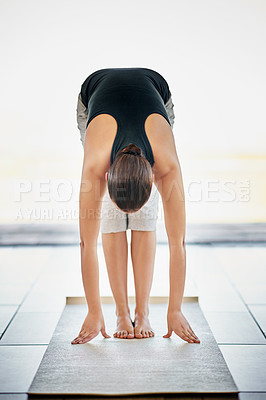 Buy stock photo Full length shot of a young woman doing yoga at home