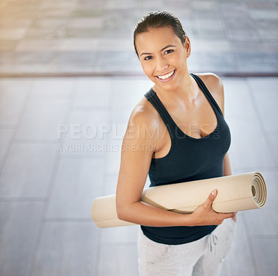 Buy stock photo Cropped portrait of a young woman carrying her exercise mat on the way to yoga