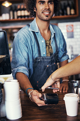 Buy stock photo Shot of a barista taking a smartphone payment from a customer at a cafe