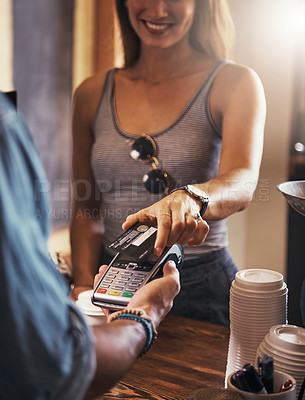 Buy stock photo Cropped shot of a woman paying for coffee with a credit card at a cafe