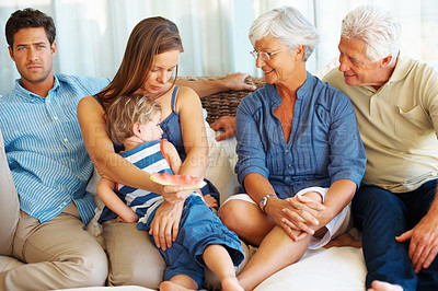 Buy stock photo Family sitting together on sofa with mother hugging kid