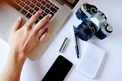 Buy stock photo High angle shot of a photographer using a laptop on her desk