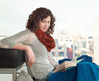 Buy stock photo Shot of a young woman reading a book at home