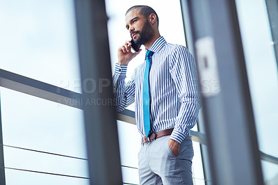 Buy stock photo Shot of a young businessman talking on a phone at the office