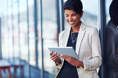 Buy stock photo Shot of a young businesswoman using a digital tablet outside of an office building