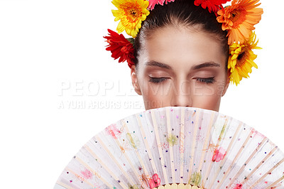 Buy stock photo Cropped shot of a beautiful young woman wearing a crown of flowers while holding a fan in front of her face