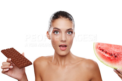 Buy stock photo Studio shot of a young woman unable to decide between a slab of chocolate or a piece of watermelon