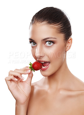 Buy stock photo Studio shot of a beautiful young woman eating a strawberry