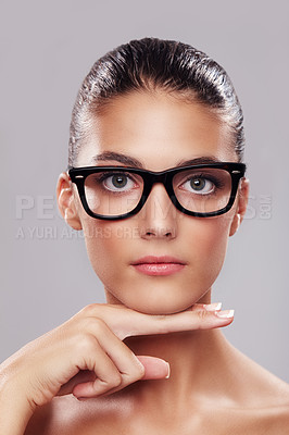 Buy stock photo Studio portrait of a beautiful young woman wearing glasses against a gray background
