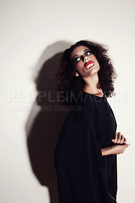 Buy stock photo Studio shot of a beautiful young fashion model with vampire teeth in her mouth