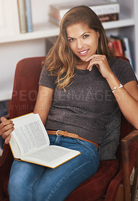 Buy stock photo Portrait of a young woman relaxing at home with a book