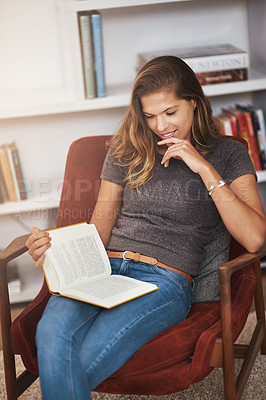 Buy stock photo Shot of a young woman relaxing at home with a book